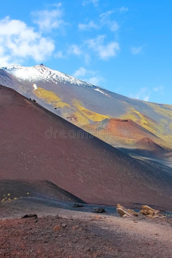 Beautiful view of Mount Etna surrounded by damaged volcanic landscape. Captured on a vertical picture from Silvestri craters. royalty free stock photography