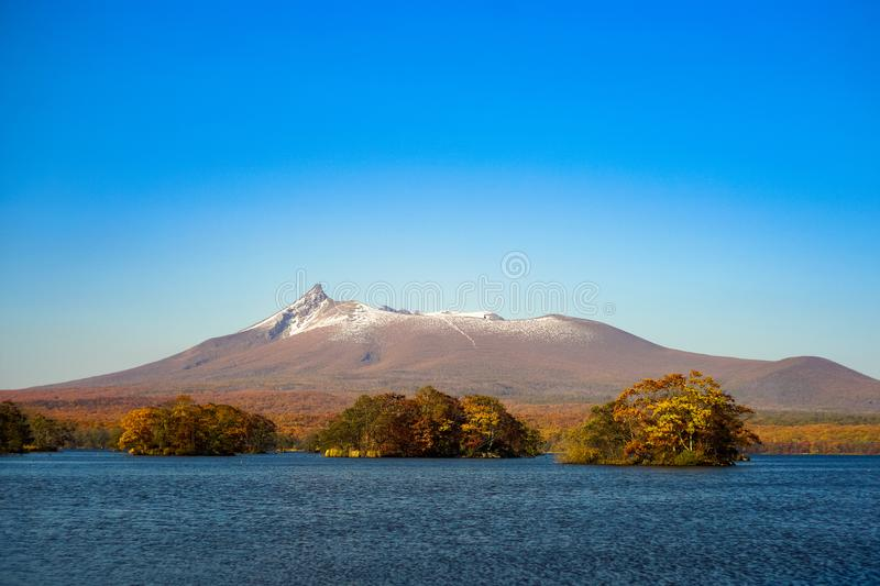 Beautiful view of Mt. Komagatake taken from Onuma park, Hakodate, Hokkaido, Japan. During autumn season with clear blue sky. stock photography