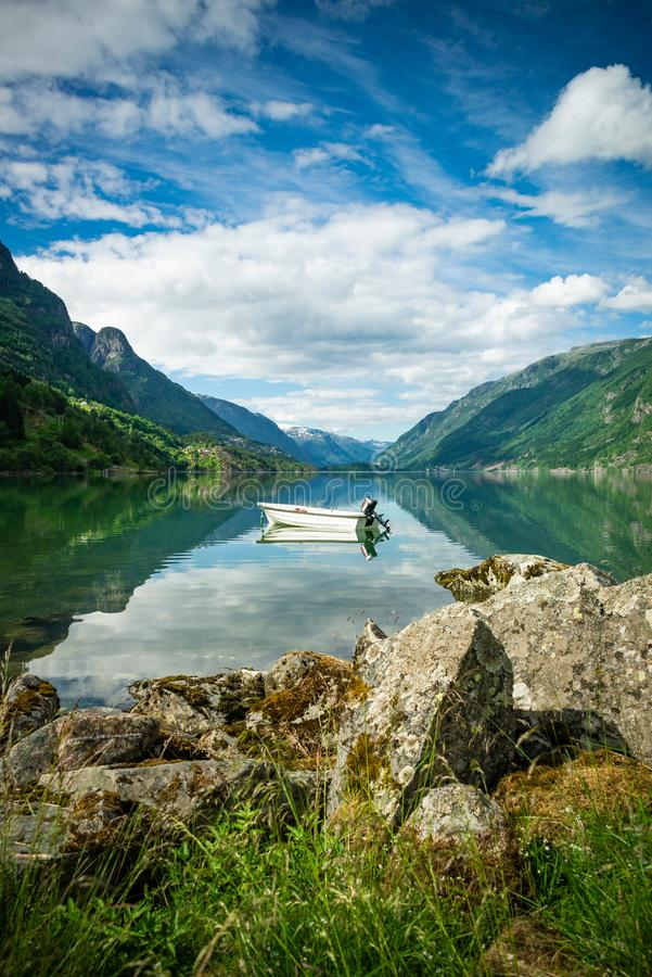 Beautiful view of the Norway fjords with a boat in calm waters. Boats moored in a calm river water among the fjords stock photography