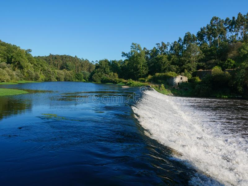 Beautiful view over Ave river in Vila do Conde, Portugal in summer. With blue sky. Water flowing over dam and trees on river bank royalty free stock photos