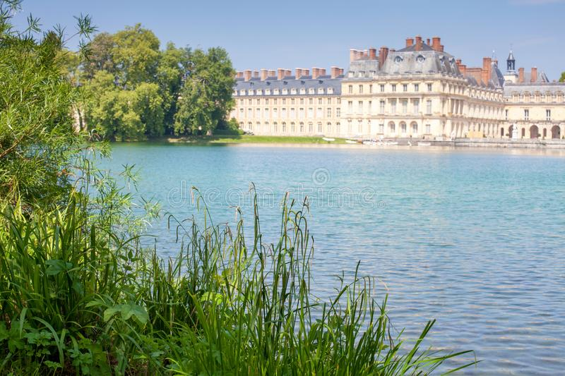 Beautiful view of the palace from the shore of the pond. Fontainebleau, France. The distant plan is blurred stock photos