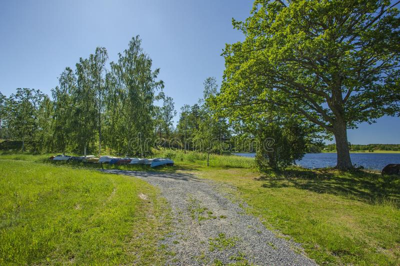 Beautiful view of parking place for small boats in the forest near lake coast line. Inverted boats under tall green trees on blue. Sky background royalty free stock image