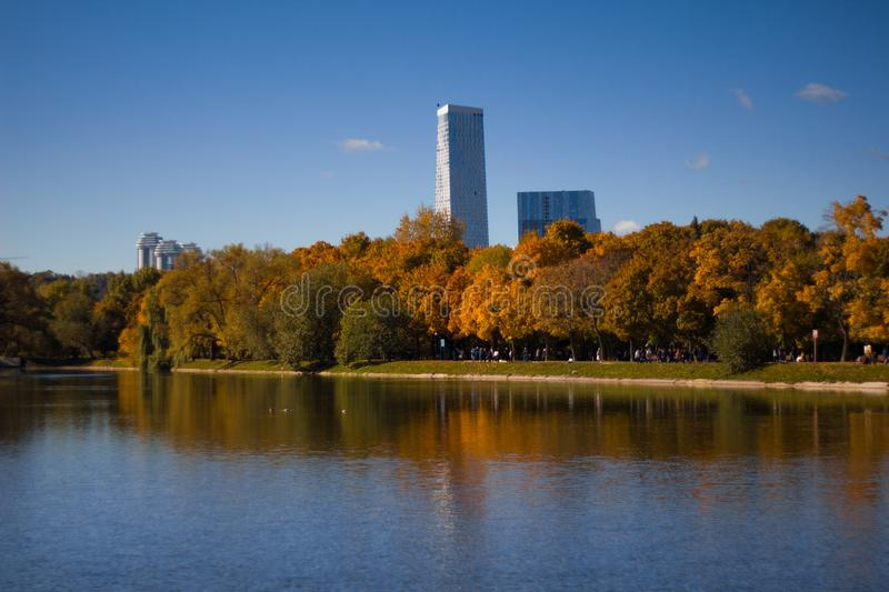 Beautiful view of the pond and yellowed trees in the Park Novodevichy convent in the fall against the blue sky and a skyscraper. royalty free stock photography