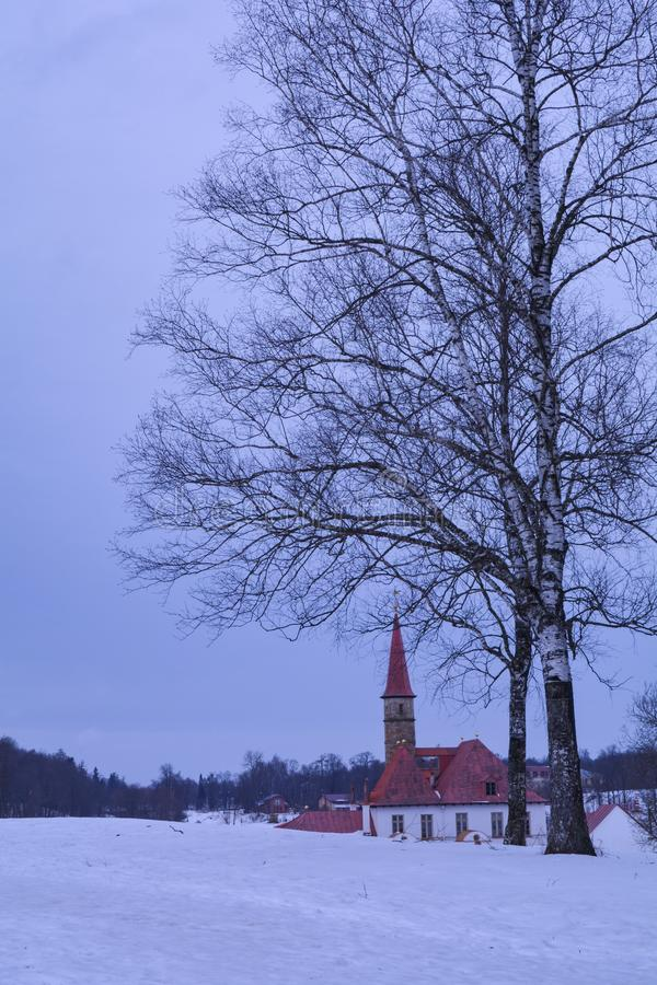 Priory Castle hid behind a birch tree. Beautiful view of the Priory Castle in a winter day. Gatchina, Russia stock image