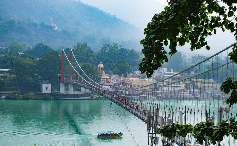 Beautiful view of Rishikesh in India `ram jhula` and `lakshman jhula` suspension bridge beautiful scenery with boat in the river g. Anges in lake in the stock photo
