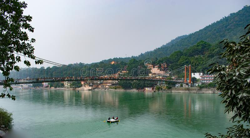 Beautiful view of Rishikesh in India `ram jhula` and `lakshman jhula` suspension bridge beautiful scenery with boat in the river g. Anges in lake in the stock photography