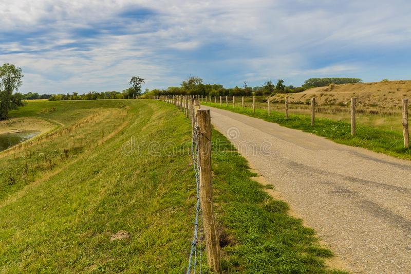 Beautiful view of a road, fenced with wooden poles and barbed wire in the middle of a field. Wonderful day with blue sky with white clouds between Elsloo and royalty free stock photography