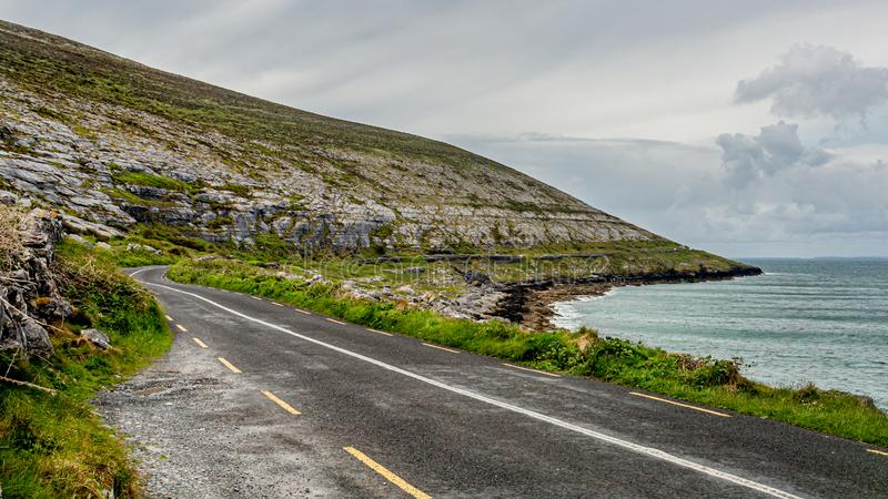 Beautiful view of the rural coastal R477 road along ​​the Burren. Geosite and geopark, Wild Atlantic Way, cloudy spring day in county Clare, west stock photos