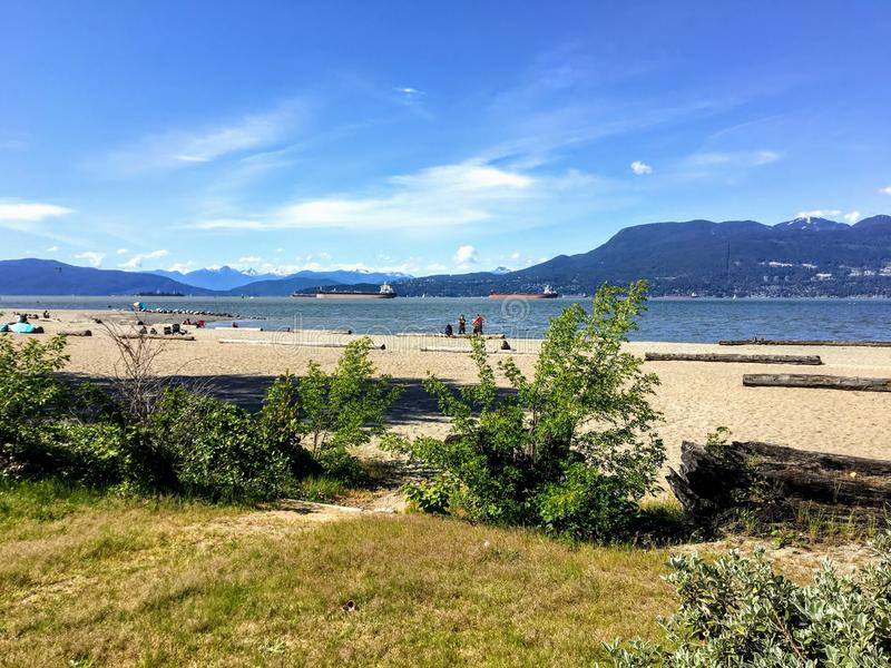A beautiful view of the sandy beaches of Spanish Banks, with tankers and mountains in the background on a beautiful sunny day. This is popular spot during the royalty free stock photography