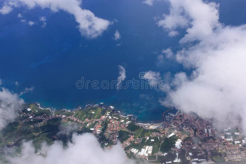 Beautiful view of the sea and the coast of the island of San Miguel from the porthole of the plane. White clouds over the atlantic stock photos