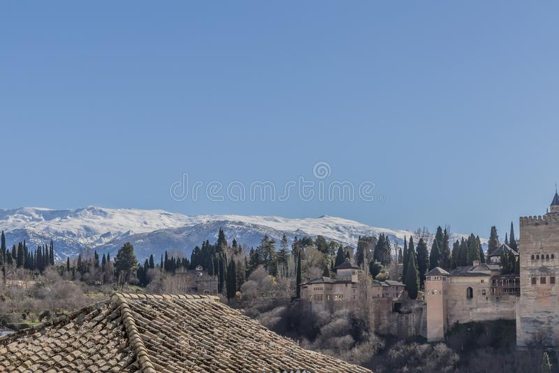 Beautiful view of snowy mountains, trees on a hill, a tile roof and a small part of the Alhambra. A wonderful sunny day with a blue sky in Granada Spain stock photo