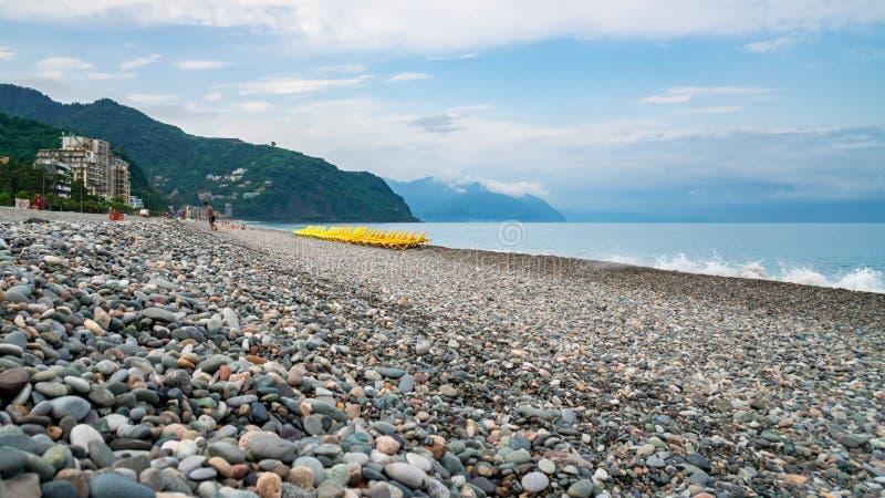 Beautiful view of the stony beach in kvariati, Adjara. deck chairs on the beach. Travel stock photography