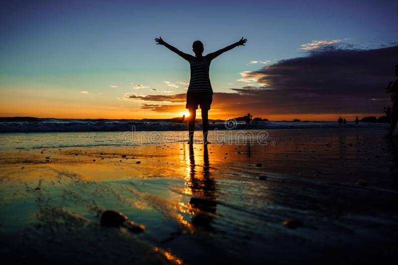 Freedom concept. silhouette girl with open arms walking on sand beach during sunset. Reflections royalty free stock image