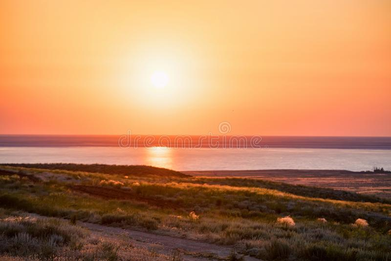 Beautiful view of sunset at salt lake Baskunchak in Astrakhan region, Russia. Picturesque landscape with dusk at salt lake Baskunchak in Russia in evening for royalty free stock photography