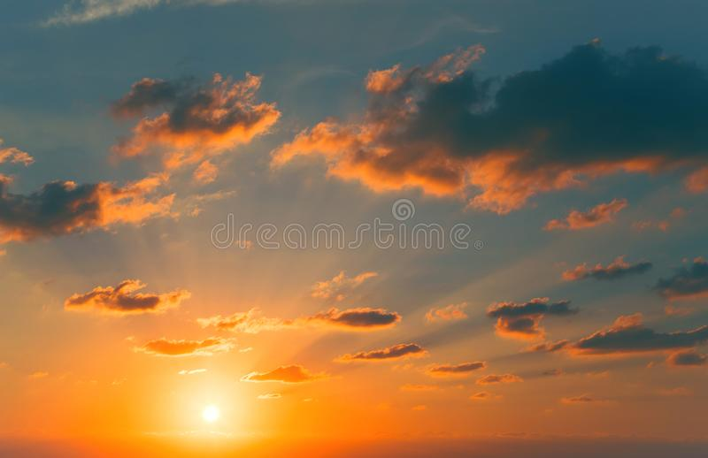 Beautiful view of a  sky with sun, sunrays and clouds. Nature summer background. Beautiful view of a sunset sky with sun, sunrays and clouds. Nature summer stock photo