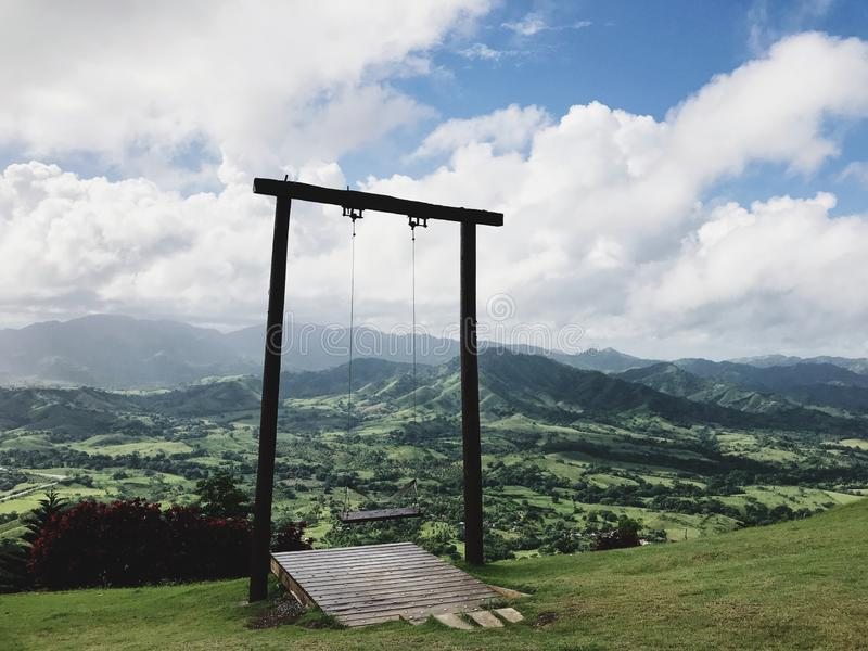 Beautiful view at the swing on the Redonda Mountain. Against green hills of Dominican Republic and the Atlantic Ocean royalty free stock photos