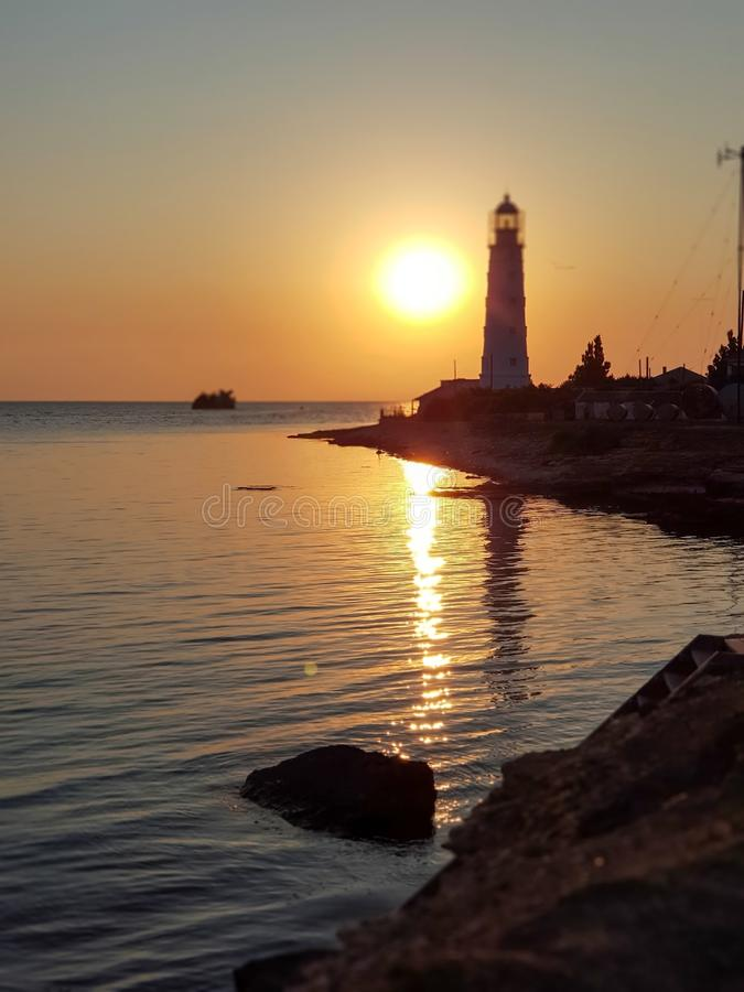 Beautiful view of the Tarkhankut lighthouse, the Black sea, the setting yellow sun on a cloudless summer day. Republic Of Crimea.  royalty free stock photography