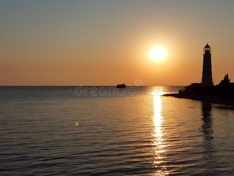 Beautiful view of the Tarkhankut lighthouse, the Black sea, the setting yellow sun on a cloudless summer day. Republic Of Crimea.  stock photo