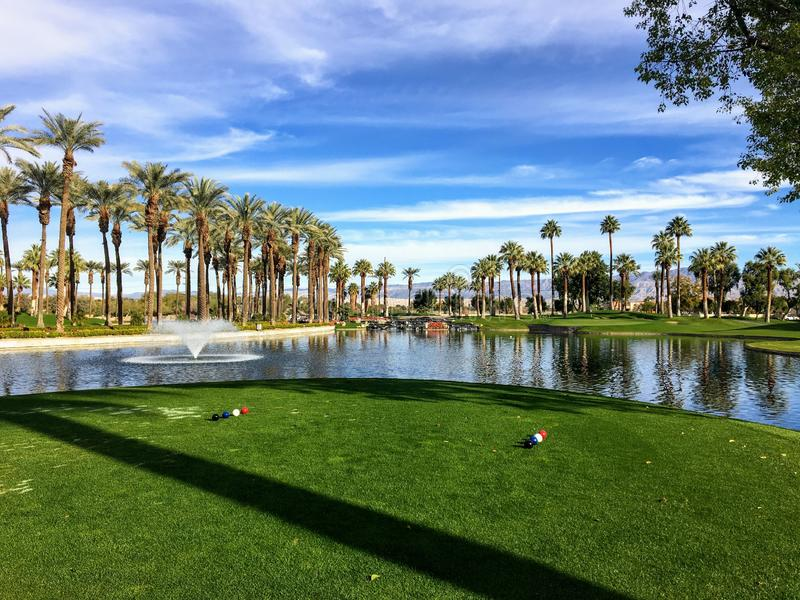 A beautiful view from the tee box of a difficult par 3 that requires a shot over the water onto an island green. Palm trees are behind the green and reflect on royalty free stock photo