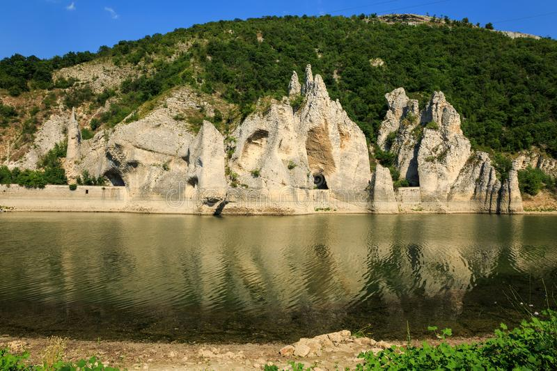 Beautiful view to the rock phenomenon. `The wonderful rocks` with reflections in the water on the shore of Tsonevo dam, near Asparuhovo Village in Bulgaria royalty free stock photography