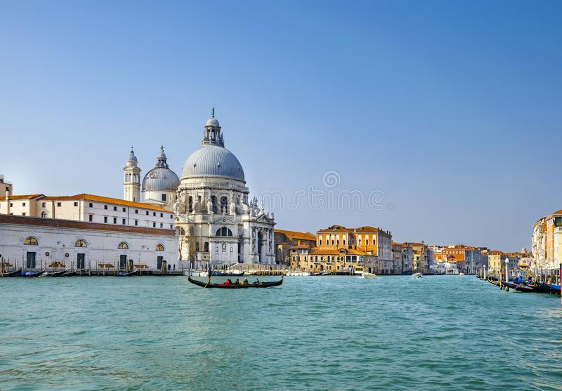 Beautiful view of traditional Gondolas on Canal Grande with historic Basilica di Santa Maria della Salute in the background on a s stock photo