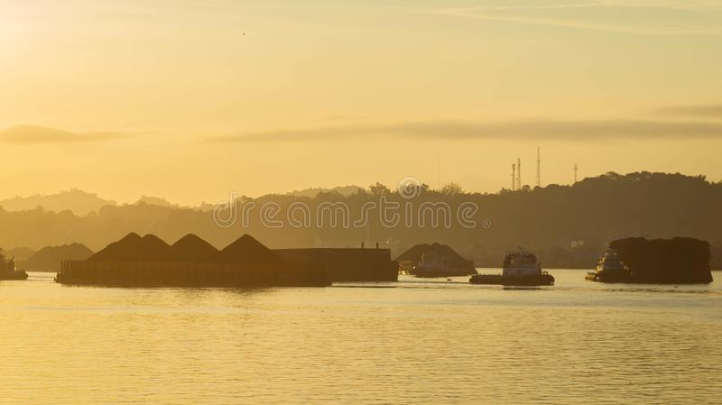 Beautiful view of traffic of tugboats pulling barge of coal at Mahakam River, Samarinda, Indonesia at dawn. Mining and cargo industry background stock photography