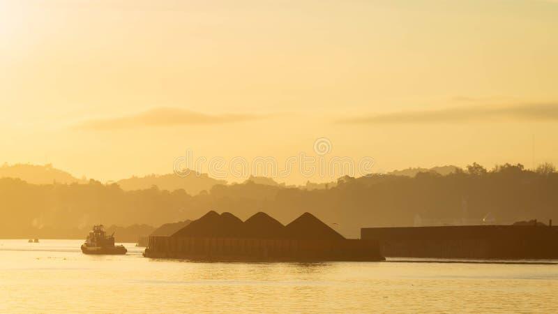 Beautiful view of traffic of tugboats pulling barge of coal at Mahakam River, Samarinda, Indonesia at dawn. royalty free stock photo
