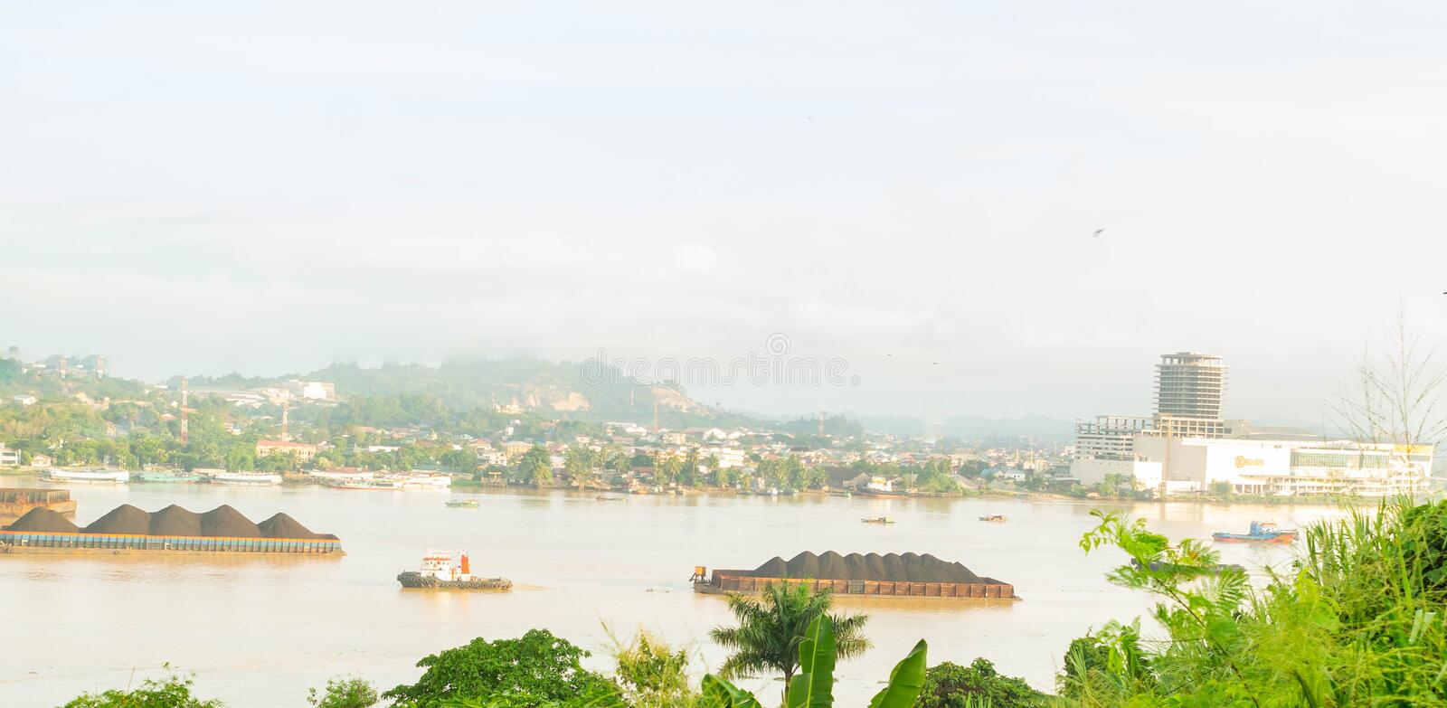 Beautiful view of traffic of tugboats pulling barge of coal at Mahakam River, Samarinda, Indonesia. Mining and cargo industry background stock photography