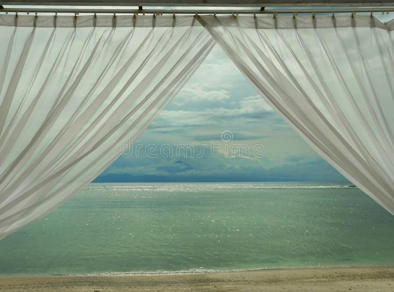 Beautiful view of tropical beach at Gili island beach of Lombok in Indonesia in Asia through luxury resort window room with stock photography