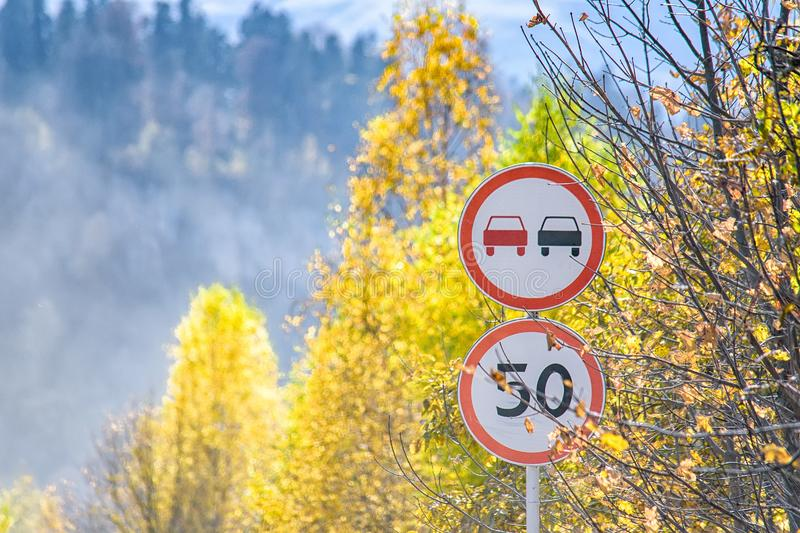 View of two road signs in autumn mountains. Beautiful view of two road signs next to yellow trees in fall royalty free stock photography