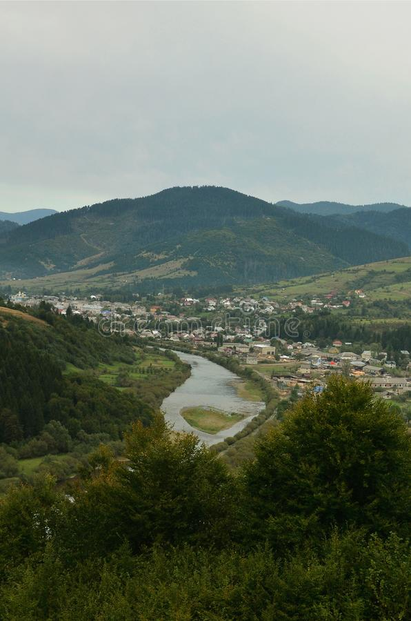 A beautiful view of the village of Mezhgorye, Carpathian region. A lot of residential buildings surrounded by high forest mountain. S and long river royalty free stock images