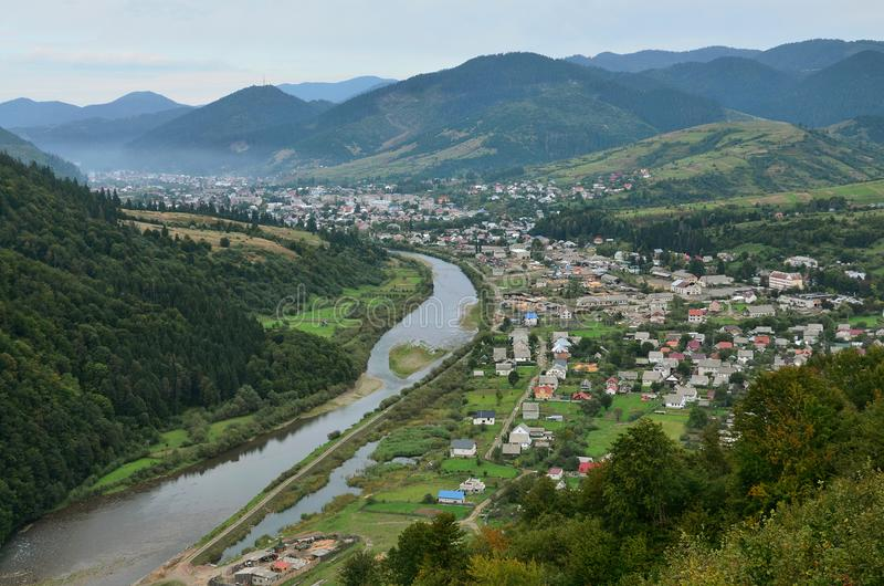A beautiful view of the village of Mezhgorye, Carpathian region. A lot of residential buildings surrounded by high forest mountain. S and long river royalty free stock photography