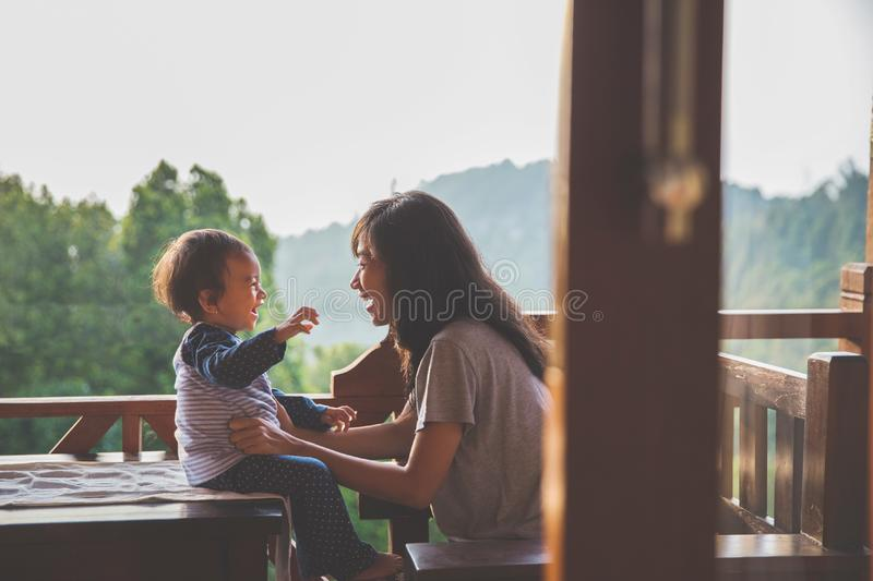 Mother playing with daughter. Beautiful view of young mother playing with daughter at the mountain background. Family vacation. Travel stock photo