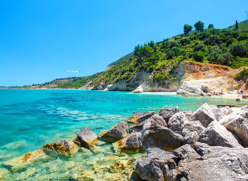Beautiful view on Zakynthos stone and sand beach, stone rocks, swimming and toasting people on the beach, blue ultramarine water o. F Ionian Sea, reefs, near to royalty free stock image