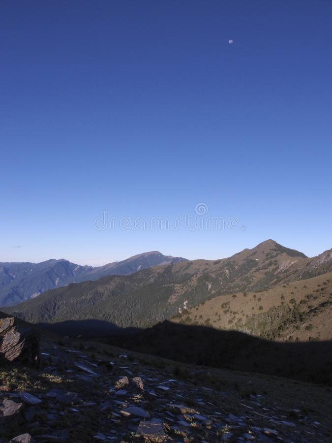 Beautiful views with highly mountains, clean blue sky, and rocks on the trail. Good for use as background. You can see the moon in this photo also royalty free stock photos