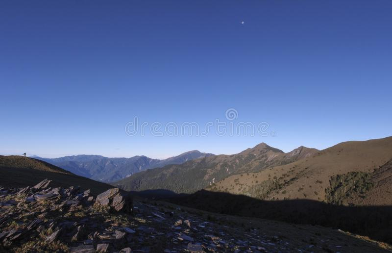 Beautiful views with highly mountains, clean blue sky, and rocks on the trail. Good for use as background. You can see the moon in this photo also stock image