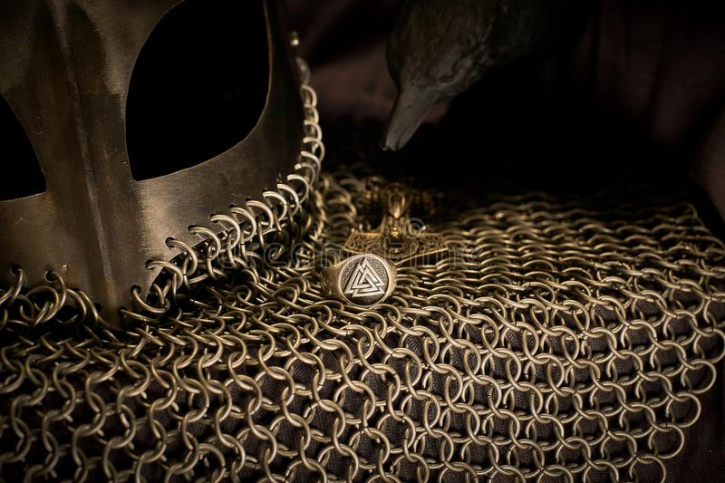 Viking Helmet and Raven, Gold. A beautiful Viking helmet next to a ring with the Valknut and one of Odin`s Ravens over a Thor`s hammer pendant stock images