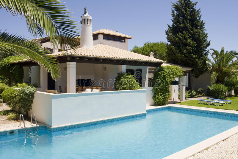Beautiful villa with a healthy garden and a pool royalty free stock photos
