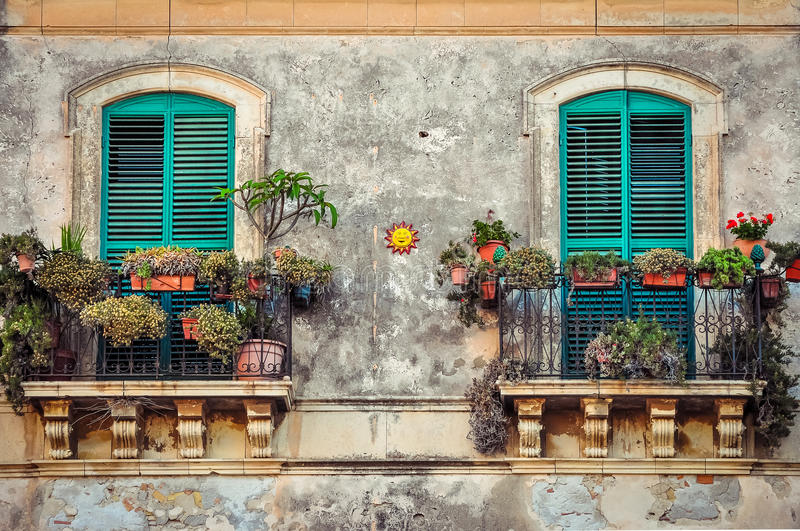 Beautiful vintage balcony with colorful flowers and doors royalty free stock photo