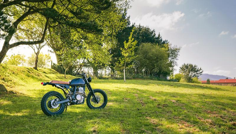 Custom motorcycle parked on the field. Beautiful vintage custom motorcycle parked on the field royalty free stock photography