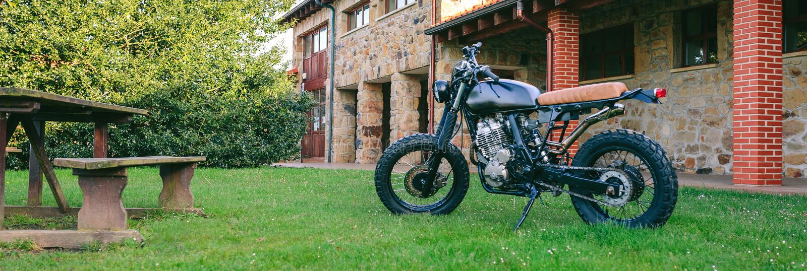 Custom motorcycle parked on the grass. Beautiful vintage custom motorcycle parked on the grass royalty free stock photo