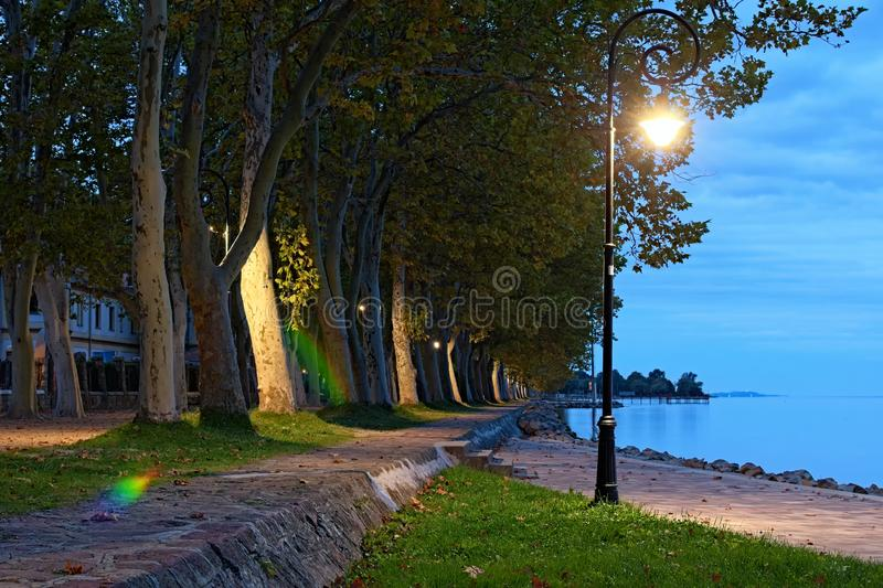 Beautiful vintage lantern near Lake Balaton. Amazing autumn morning landscape. Lake Balaton and Plane tree alley in Balatonfoldvar stock photography