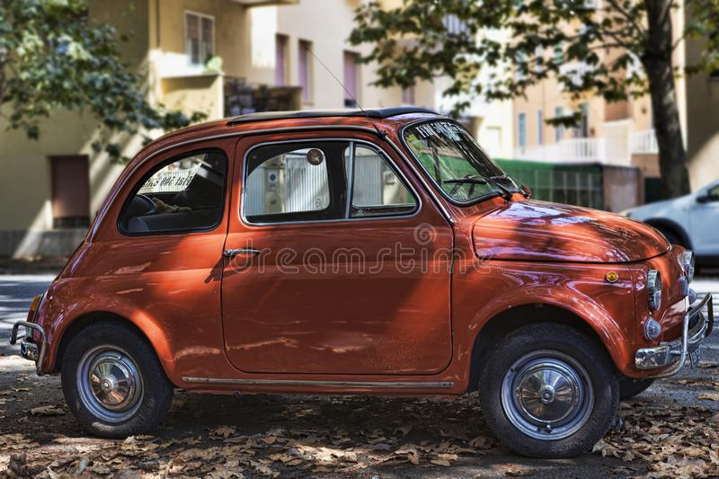 Beautiful vintage red Fiat 500 in autumn background context royalty free stock photo