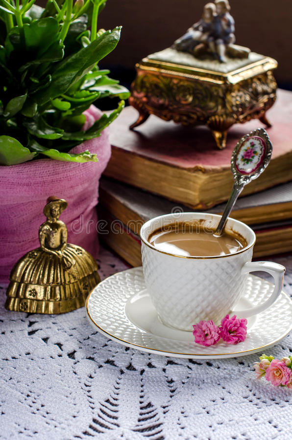 Beautiful vintage still life with flowers, books, a Cup and bell. Cup of coffee. Old books, vintage jewelry box figurines. Pink flowers. Vintage brass bells stock photos