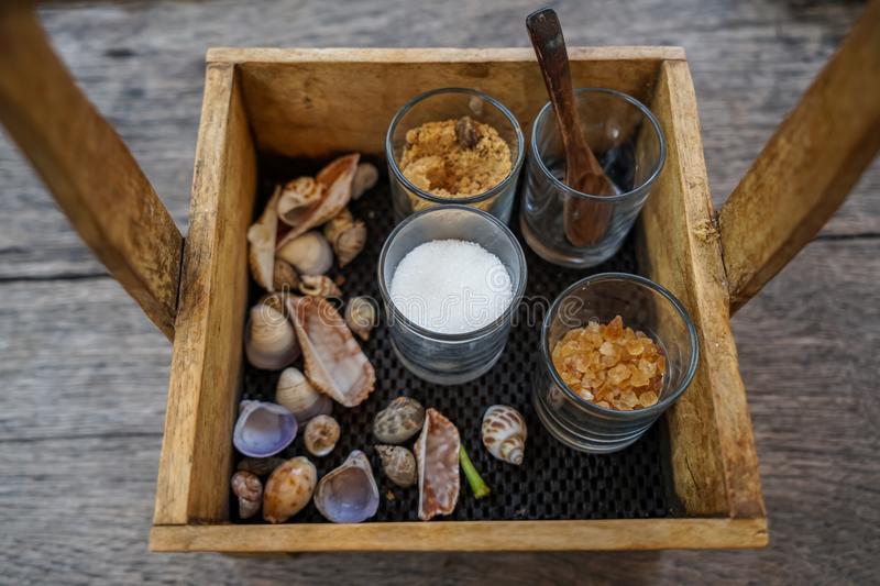 Beautiful vintage wooden box basket holding sugar glasses and spoon for coffee and tea with sea shell decoration on wooden table stock image