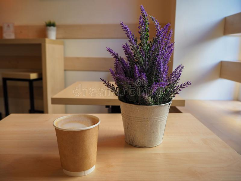 Beautiful violet lavender in a iron little bucket and a cup of coffee on the wooden table. In the cafe royalty free stock photography