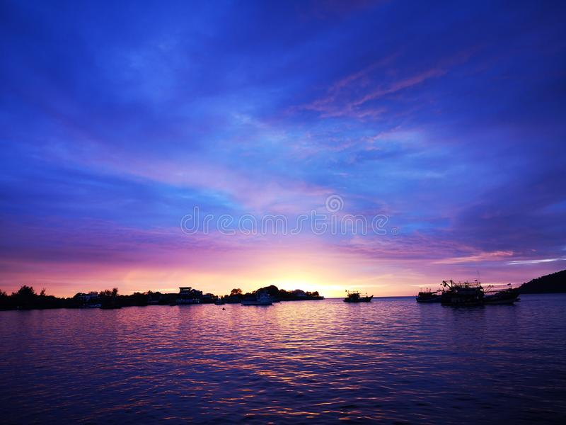 Beautiful and truly colorful sunset with blue sky above. Beautiful and vivid color sunset view along the beach with blue sky royalty free stock image
