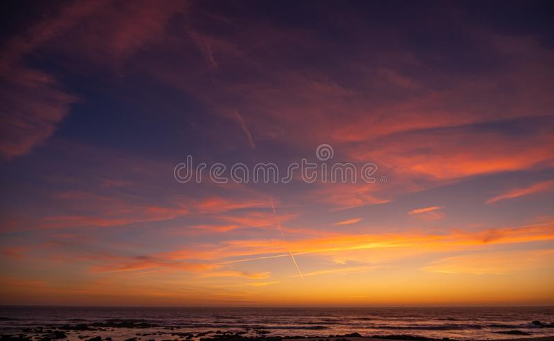 Beautiful, vivid sunset sky over ocean with red clouds and blue yellow gradient background royalty free stock images