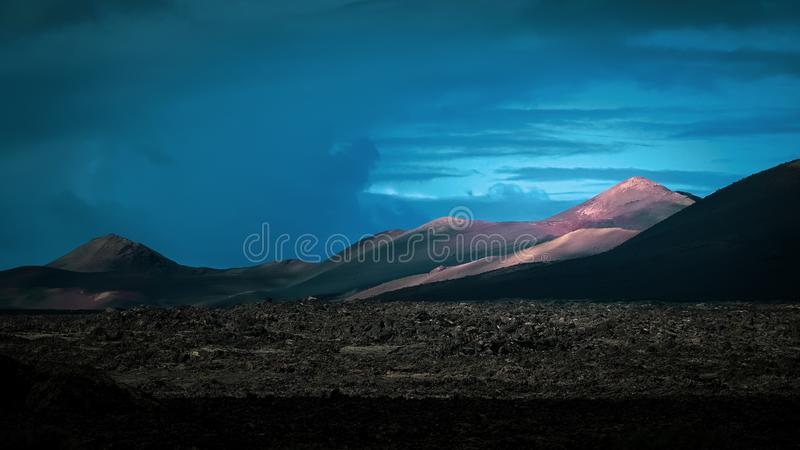 Beautiful volcanic landscape background. Mountain range with lava fields in the foreground royalty free stock image