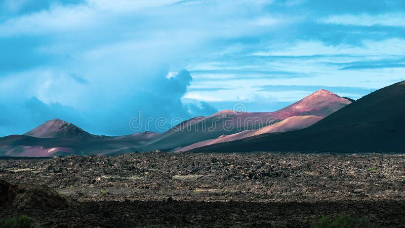 Beautiful volcanic landscape background. Mountain range with lav. A fields in the foreground royalty free stock image
